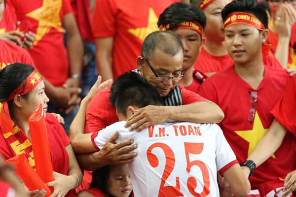 Một CĐV lớn tuổi vỗ về Huy Toàn sau trận đấu.