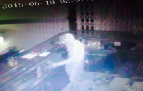 Hình ảnh camera ghi lại cho thấy tên trộm rất bình thản để lấy vàng bỏ vào bao. Ảnh: Cửu Long