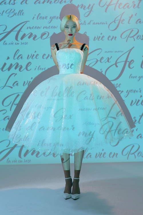 Thiết kế váy trắng ánh kim trở nên bắt mắt hơn với phần tùng váy xoè rộng tựa như trang phục của các diễn viên trong nhiều vở