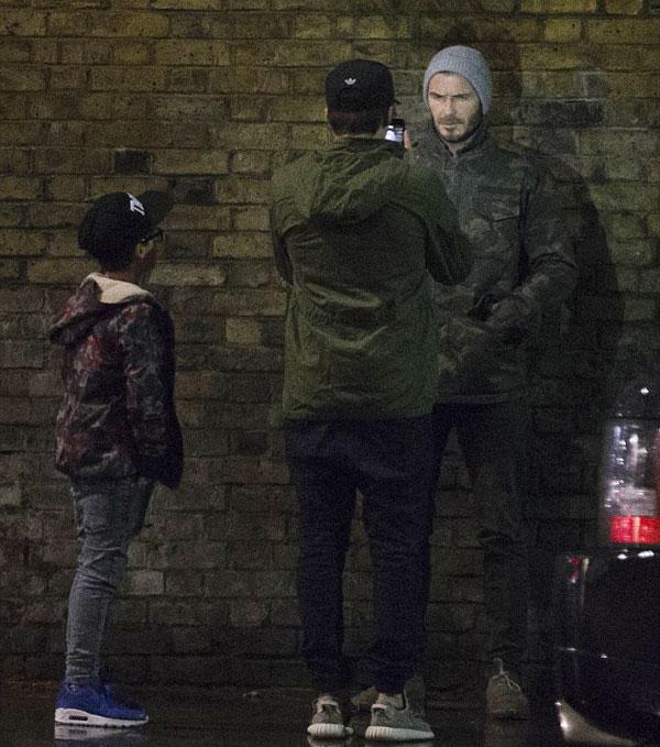 Ba bố con vừa đi vừa trò chuyện vui vẻ. Có lúc cựu danh thủ Anh dừng lại, tạo dáng lạnh lùng, dựa sát tường để cậu cả Brooklyn chụp ảnh.