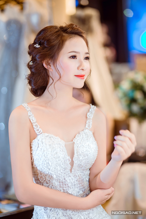 [Caption]Kiểu tóc búi thấp phù hợp với những cô dâu diện váy trễ vai, khoét cổ V sau lưng.