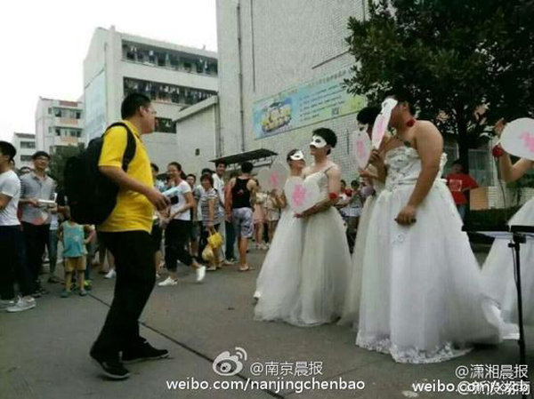 The professor donned a white wedding dress and a mask to throw what looks to be an elaborate proposal with the help of some friends who wore white dresses and even preformed live music.