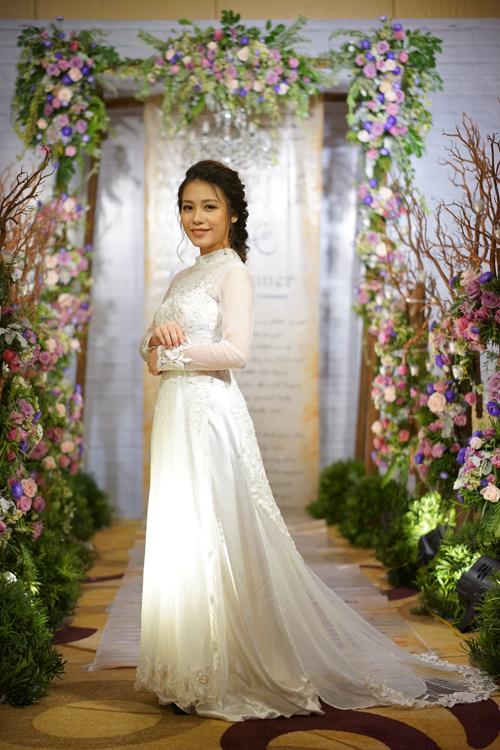 [Caption]Áo dài cưới màu trắng nhẹ nhàng nhưng cũng không kém phần sang trọng vì cách đính kết điệu đà. Hoa văn cùng tone màu áo được trang trí ở ngực và tay áo giúp thiết kế đồng điệu, hài hòa về màu sắc.