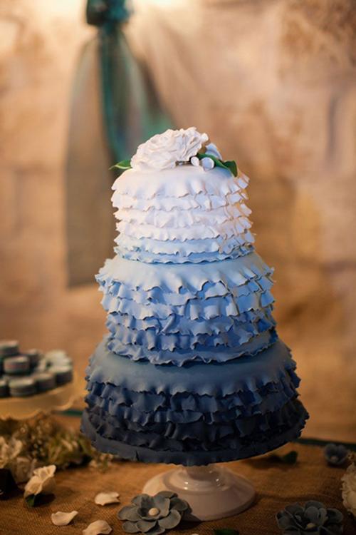 [Caption]Kiểu bánh và cách kết hợp màu sắc từ đậm tới nhạt khá đa dạng, tùy theo màu chủ đạo của đám cưới và sở thích của cô dâu chú rể nhưng bánh thường có những chi tiết bèo nhún mềm mại để màu sắc chuyển tiếp được nhẹ nhàng.
