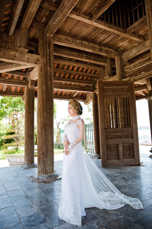 [Caption]Nữ người mẫu hóa cô dâu trong mẫu áo dài trắng đính 3D điệu đà, lấy cảm hứng từ váy cưới. Nhà thiết kế tạo điểm nhấn đối xứng ở vai, ngực, eo và ống tay bằng pha lê và cườm cầu kỳ.