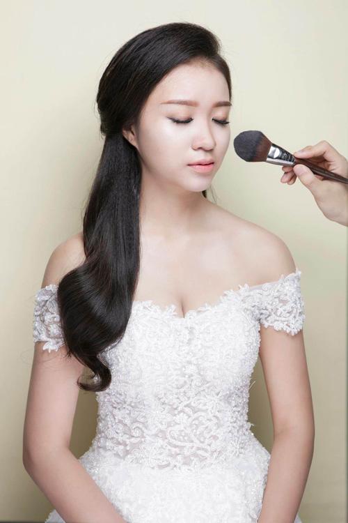 [Caption] Sau các bước dưỡng da căn bản, chuyên gia trang điểm tán một lớp nền mỏng rồi sử dụng cọ che khuyết điểm để che vùng mắt thâm, vết đỏ của mụn, các vùng da không đều màu.