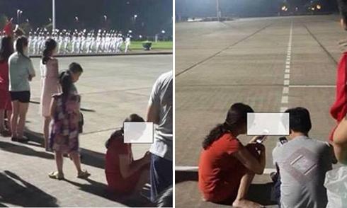 Đôi vợ chồng ngồi, dùng điện thoại trong lễ hạ cờ ở lăng Bác