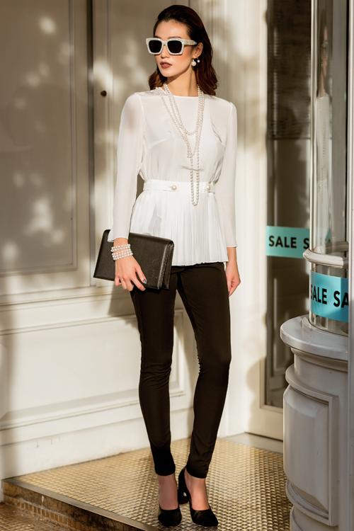 Áo lụa trắng tay dài kín đáo với điểm nhấn phần eo tạo sự thon gọn kết hợp cùng quần đen dạng leging dễ dàng tôn dáng vẻ thanh mảnh của Khánh My.