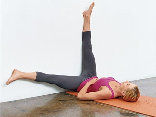 Nằm ngửa trên sàn, hai chân duỗi trên tường, ngửa lòng bàn chân hướng lên trần nhà - Từ từ gạt chân trái sang trái, sau đó lại đưa về vị trí cũ - Lặp lại tương tự với chân phải
