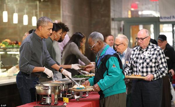 Nhân dịp Lễ Tạ ơn, Tổng thống Mỹ Barack Obama cùng Đệ nhất phu nhân Michelle và con gái út Sasha có chuyến thăm tới Viện dưỡng lão Lực lượng vũ trang ở Washington. Gia đình ba người đích thân phục vụ đồ ăn cho các  cựu chiến binh ở viện. Ảnh: AFP