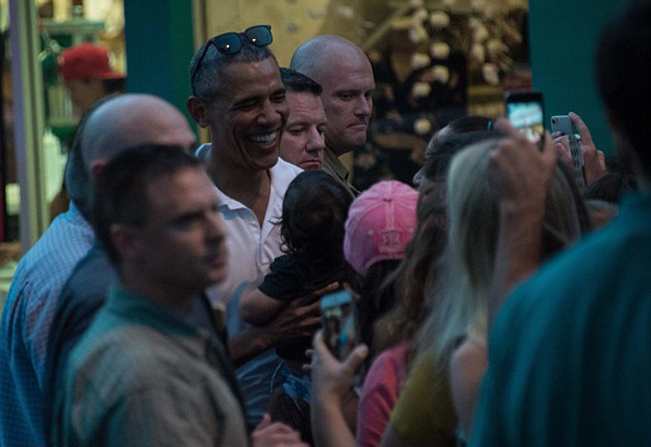 The president, wearing casual clothes and flip flops, shook hands and spoke with a small crowd outside the store.
