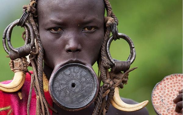 Các cô gái bộ tộc Mursi ở Ethiopia đặt một đĩa tròn ở môi dưới  để căng môi ra, và họ không ngừng tăng kích thước đĩa tròn làm bĩu môi. Phong tục này là một biểu tượng của sắc đẹp và sự trưởng thành về mặt tình dục.