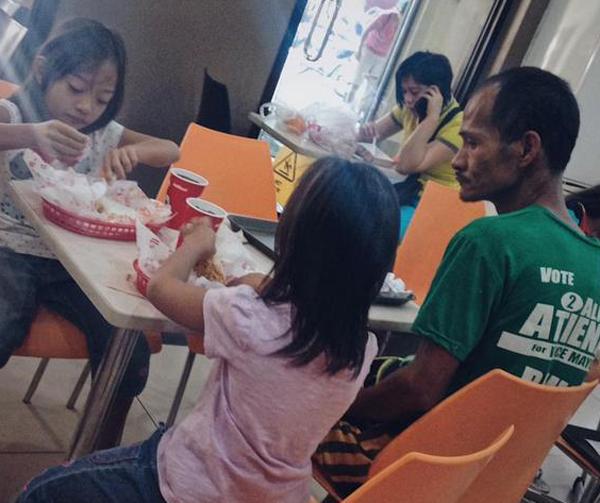 Bức ảnh anh Ryan Arebuabo ngồi nhìn hai con ăn gà rán khiến nhiều người xúc động. Ảnh: AsiaOne