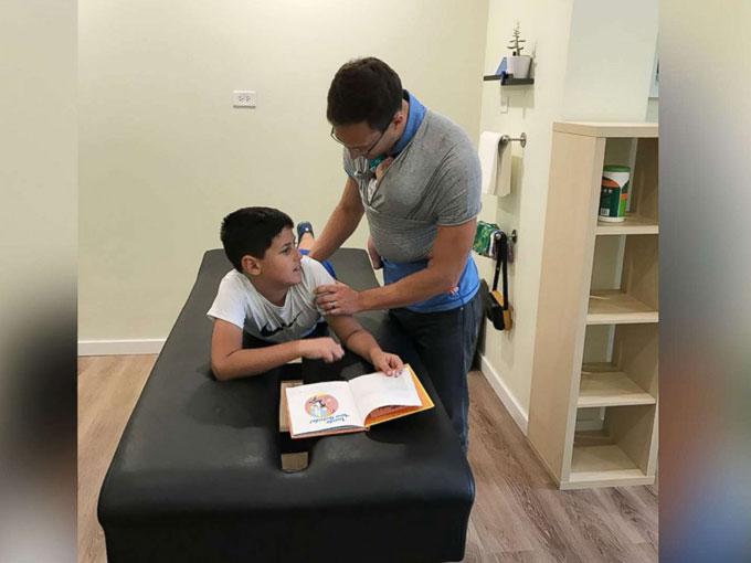 Bác sĩ vừa địu con vừa thăm khám bệnh nhân