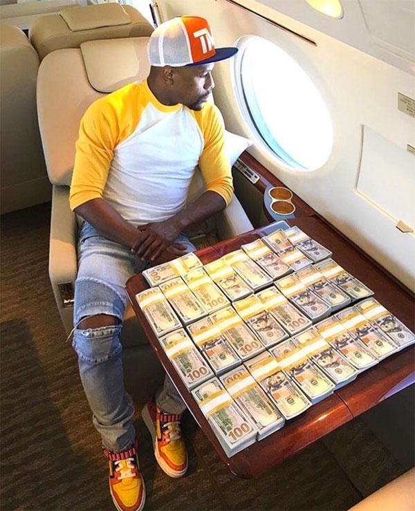 Mayweather trầm tư ngồi trước bàn bày kín cọc tiền
