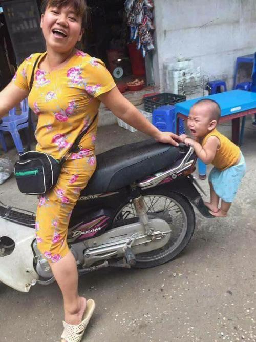 be-trai-bam-duoi-xe-may-doi-theo-me-di-cho-1