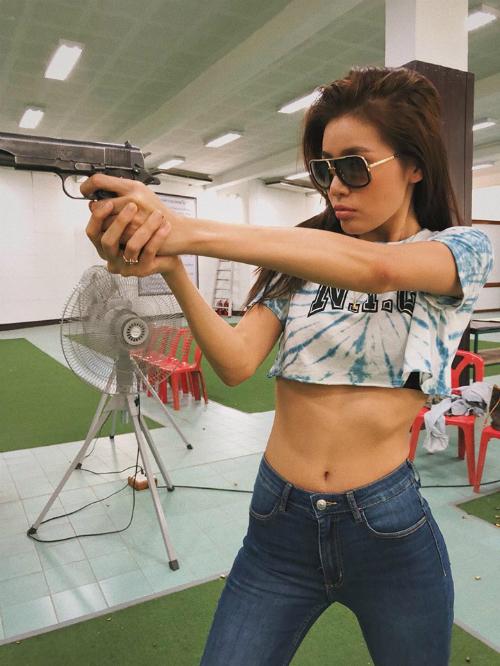 Minh Tú mặc áo croptop khoe eo thon săn chắc khi tập bắn súng.