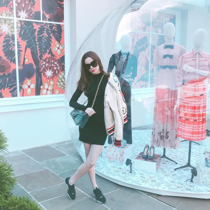 Áo khoác nỉ trang trí họa tiết bắt mắt được người đẹp phối cùng váy ôm đen, giầy thể thao. Phụ kiện đi kèm là túi đeo chéo có họa tiết để thể hiện tinh thần ton-sur-ton cùng áo khoác.