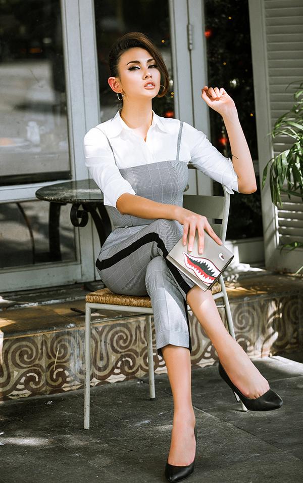 Hoà cùng trào lưu diện trang phục kẻ sọc ca rô được ưa chuộng ở mùa mốt 2017/2018, siêu mẫu chọn áo hai dây đồng bộ với quần ống côn để mix cùng sơ mi trắng dáng cơ bản.