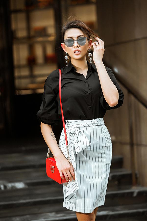 Chân dài nổi tiếng của làng mẫu Việt gợi ý xây dựng hình ảnh quý cô văn phòng sành điệu với sơ mi đen biến tấu, chân váy bút chì điệu đà, kính mắt hợp mốt, hoa tai to bản và túi đeo chéo gam màu rực rỡ.