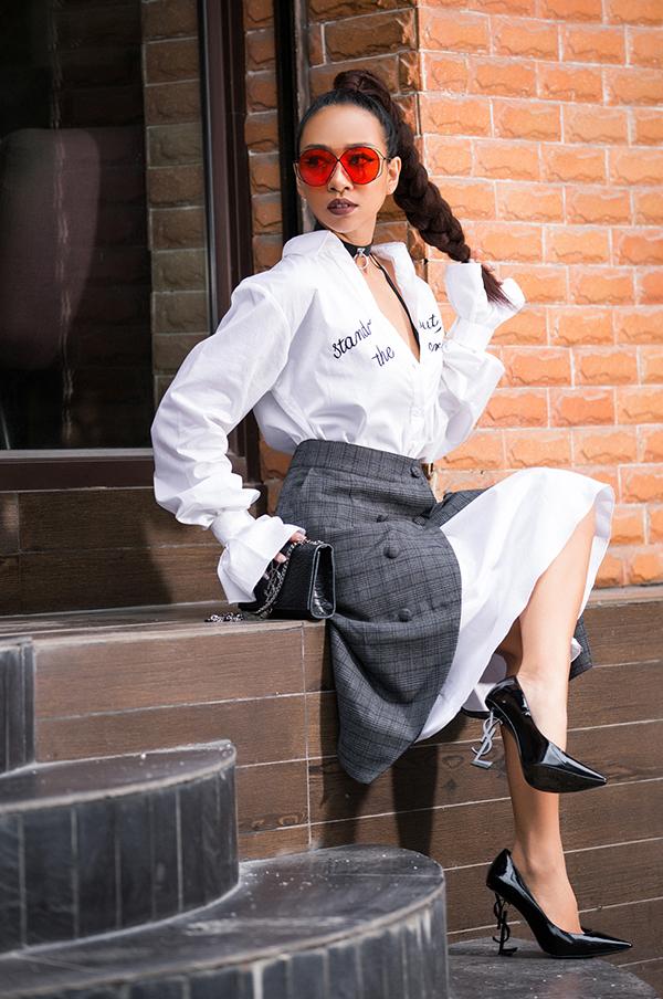 Ca sĩ Thảo Trang chọn chân váy cài nút để phối cùng áo sơ mi phom dáng rộng. Phụ kiện đi kèm là vòng choker, giày mũi nhọn và túi midi tiệp sắc đen.