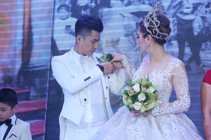 Lâm Khánh Chi chu đáo giúp chú rể cài lại hoa trên ngực áo.