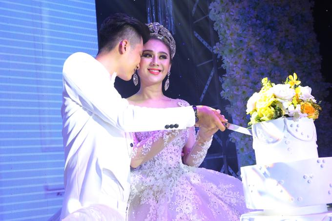 Đôi vợ chồng chung tay cắt bánh cưới.