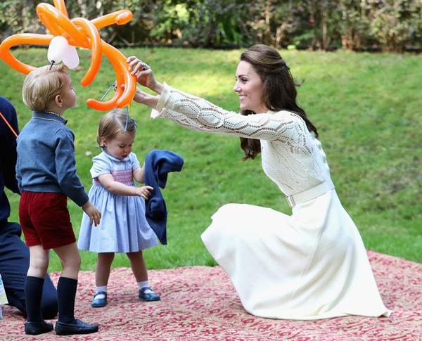 Kate ngồi xuống để ngang tầm nhìn với con trai trong khi đang bế công chúa nhỏ. Ảnh: AP.