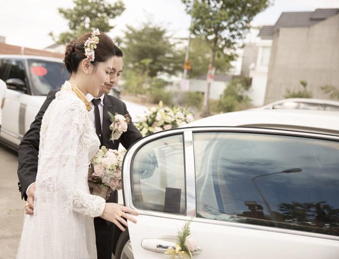 Chú rể dìu cô dâu ra xe hoa.