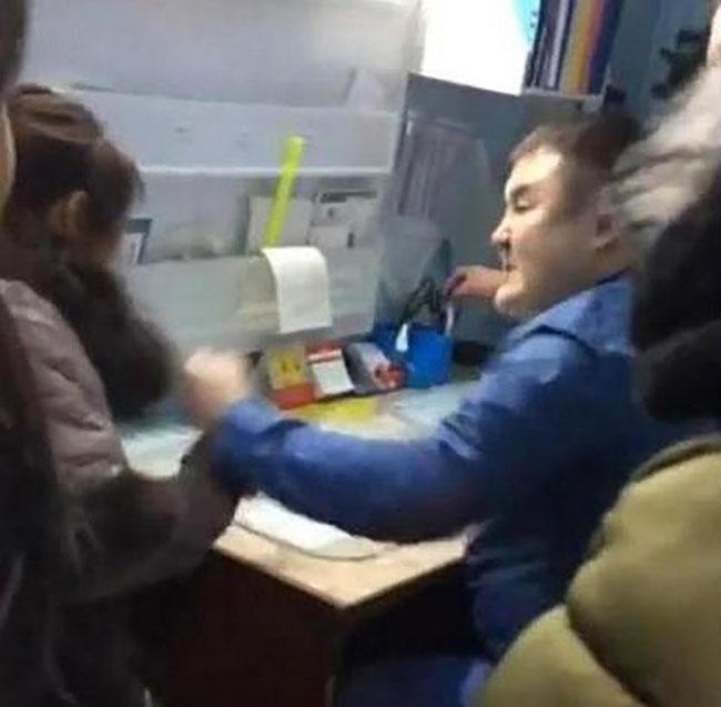 Bác sĩ ngồi ở bàn khám đánh bệnh nhân của mình.