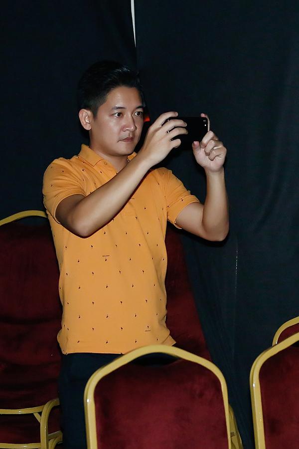 Nam diễn viên chăm chú ghi lại hình ảnh của Hải Băng khi cô hát.