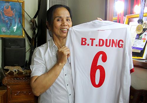Bà Dương Thị Hương ăn mừng chiến công của con trai cùng đội tuyển bên chiếc áo đấu. Ảnh: Hùng Lê