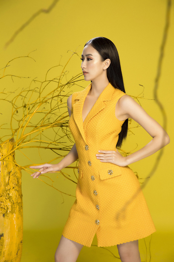 Váy cổ vest phom dáng hiện đại được thêm điểm nhấn bằng nút hoa mai kim loại có độ bắt sáng cao.