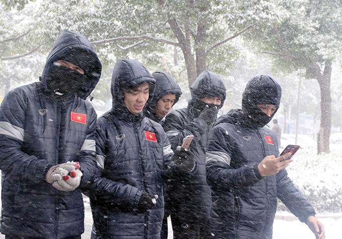 Công Phượng cùng đồng đội móc điện thoại chụp selfie trong cơn mưa tuyết.
