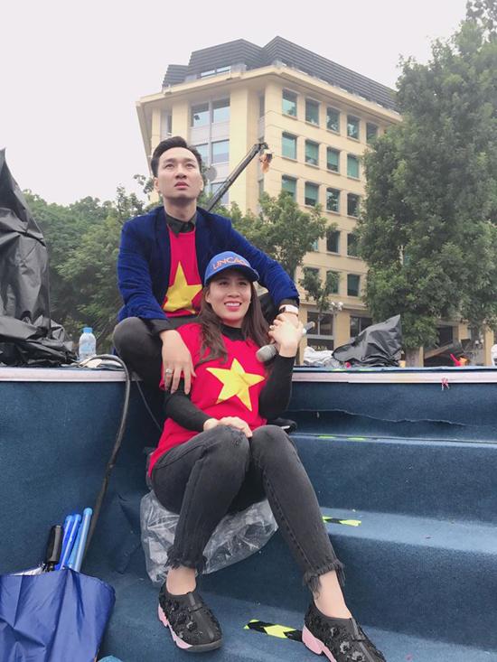 Hai vợ chồng Thành Trung ngồi bệt ở sàn sân khấu để theo dõi trận chung kết từ màn hình led.