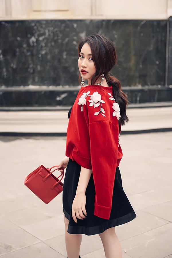 Tông đỏ đen được hoà quyện cùng nhau trên set đồ gồm áo khoác lửng, chân váy xoè, phụ kiện đi kèm là túi xách cỡ trung và hoa tai ánh kim.