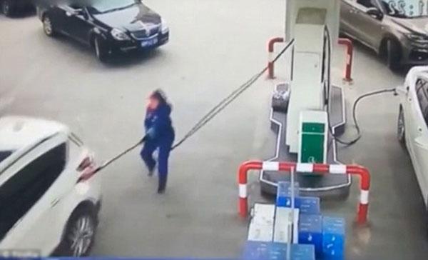 Nhân viênđang kiểm tra đồng hồ bơm xăng thì chiếc xe bất ngờ chuyển bánh.