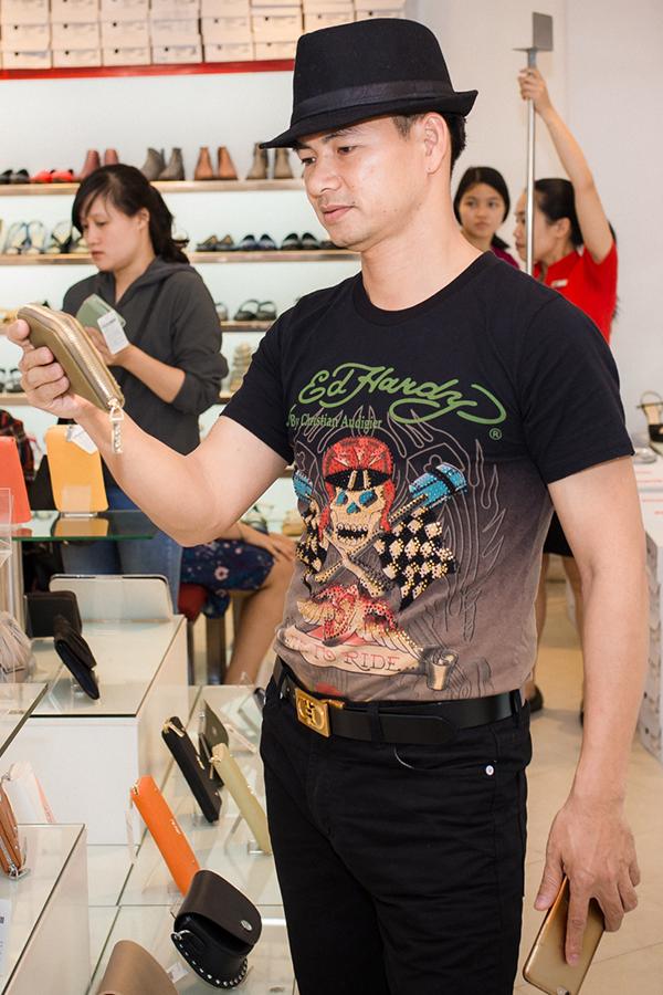 Nghệ sĩ Xuân Bắc săm soi chiếc ví mà anh định mua tặng bà xã.
