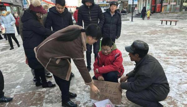 Những người qua đường dừng lại cho Zhang tiền sau khi biết cậu bé đang ăn xin để cứu mẹ. Ảnh: SCMP