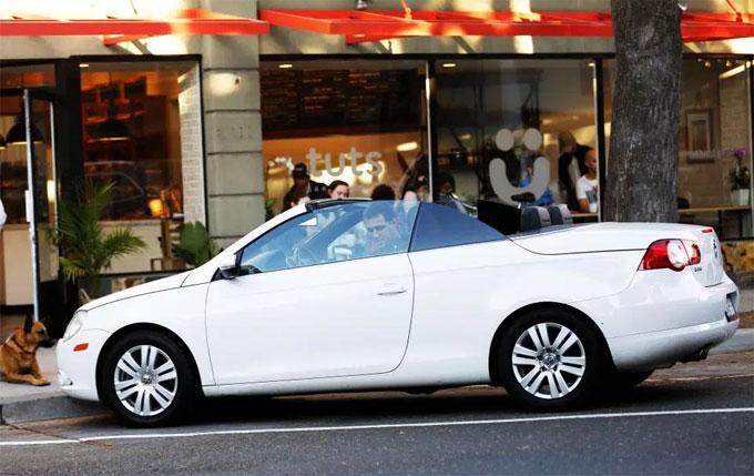 Hakan Sukur lái xe mui trần trước cửa hàng của anh tại Mỹ.