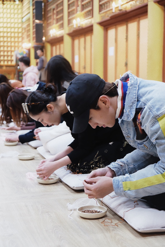 Khi ghé thăm chùa Woljeongsa nằm sâu trong vùng núi thành phố Pyeongchang, Văn Mai Hương và Bình Anđã cótrải nghiệm xâutràng hạt bằng gỗ. Cả hai mất khoảng hơn 1 giờ đồng hồ để hoàn thành nghi lễ theo hướng dẫn của một sư thầy. Bình An cho biết, trước khi xâu một hạt vào dây, anh và những người bạn đồng hành phải tiến hành lạy một lần. Tràng hạt gồm 108 hạt, tượng trưng cho 108 vị La Hán. Việc xâu tràng hạt bao hàmý nghĩa giúp con người gạt bỏ mọi phiền não và cầu mong những điều tốt đẹp cho cuộc sống.