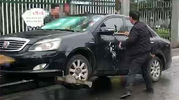 Chủ xe lấy búa đập vào thân xe và cửa kính.