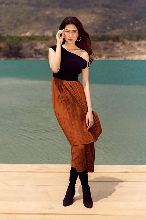 Áo thun ôm tôn đường cong được bố trí thêm đường lệch vai để khiến hình ảnh của người mặc trở nên sexy hơn. Thiết kế áo ôm sát hình thể được phối cùng chân váy dập ly màu ánh kim hợp mốt.