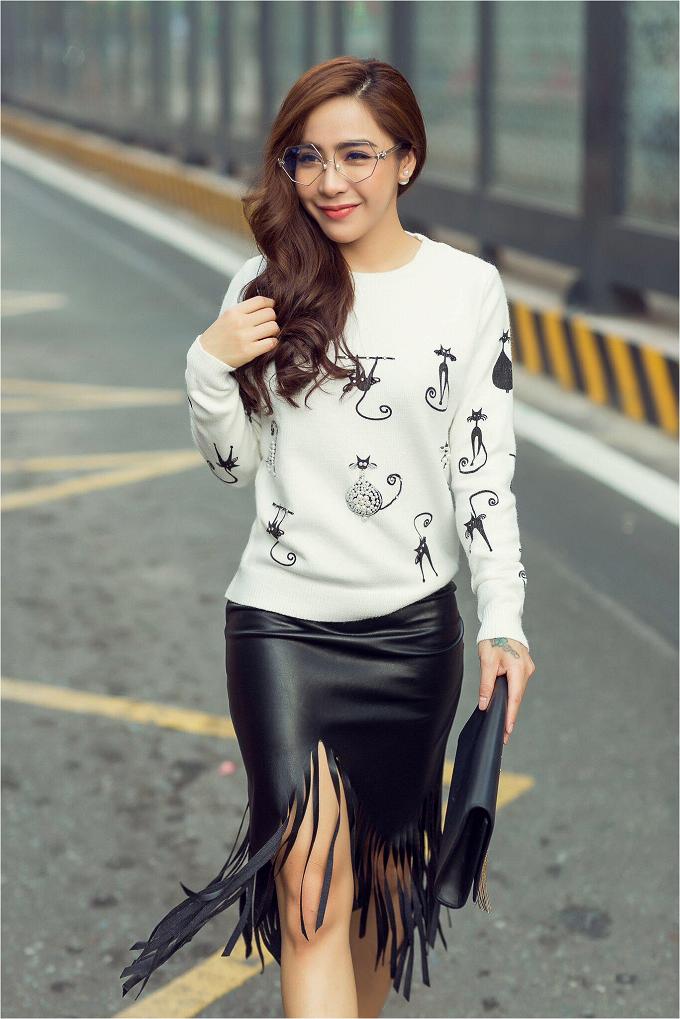 Với những cuộc gặp gỡ đối tác không quá trang trọng, Mai Diệu Linh chọn một chiếc áo len nhẹ nhàng dáng basic màu trắnghọa tiết màu đen kết hợp với váy da tua ruaton sur ton vừalịch thiệp lại vừacá tính và gợi cảm.