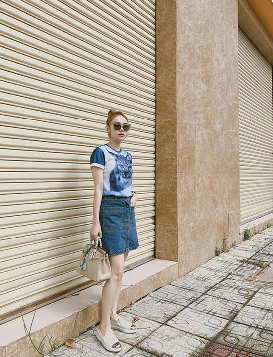 Chân váy jean cài nút là trang phục được ưa chuộng ở mùa hè năm ngoái, bước vào mùa thời trang mới nó vẫn được nhiều bạn trẻ yêu thích. Minh Hằng chọn áo thun hoạ tiết hình mèo có tông màu đồng điệu cùng chân váy, cô kết hợp thêm túi xách Hermes, giày slip on để phối đồ.