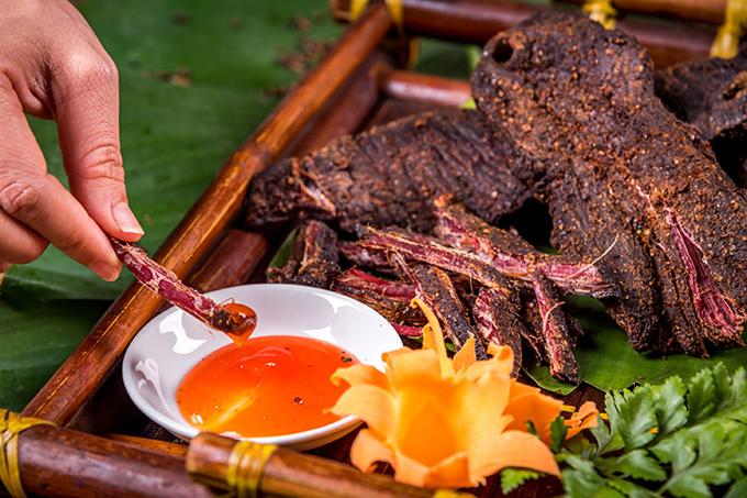 Thịt trâu gác bếp: Đây là món nhất định bạn phải nếm thử một lần đến Tây Bắc. Miếng thịt mang hương vị đậm đà nhờ kỹ thuật ướp gia vị cầu kỳ và tinh tế. Thịt săn lại và có màu đen óng sau thời gian gác bếp hun khói đủ độ. Miếng thịt ám khói bếp lâu ngày có vỏ khô, bên trong còn hơi ướt mềm và mang đậm phong vị núi rừng. Khi thưởng thức, bạn nên nướng qua, sau đó dùng chày đập giập, xé nhỏ và chấm cùng tương ớt, hoặc ớt cay trộn muối hạt giã nhỏ.