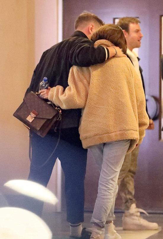 Selena ra về trước cùng một cậu bạn. Hai người choàng tay nhau khá thân mật.