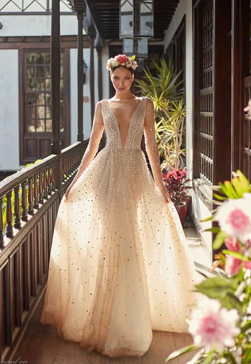 Váy cưới tone nude đính kim sa với đường xẻ cổ chữ V sâu hun hút.