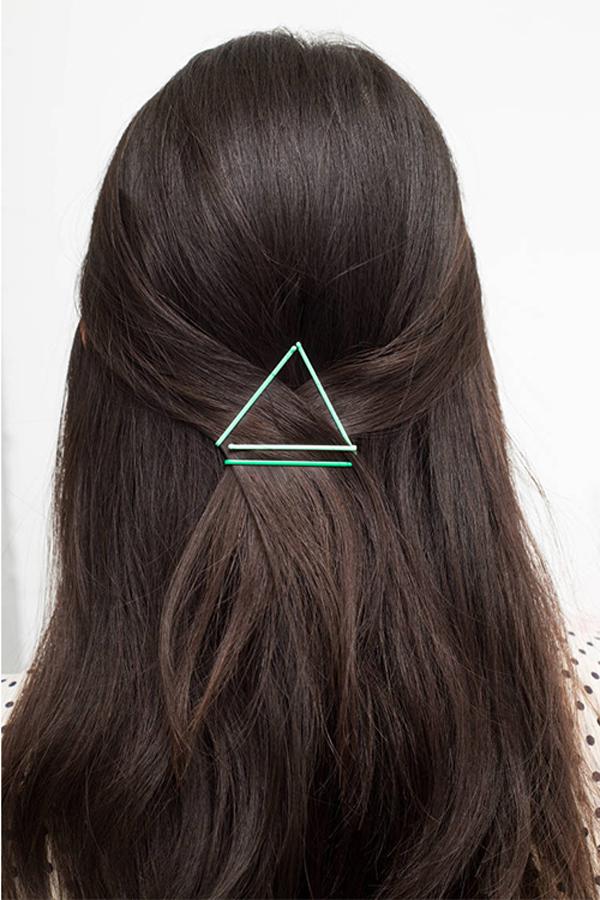 Kiểu tóc buộc nửa đầu bớt phần đơn điệu nhờ ba chiếc cặp tăm tạo hình.