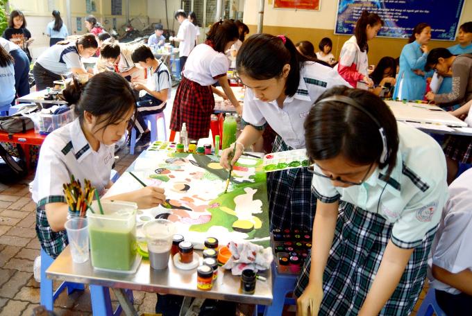 Ngoài phần thi cá nhân trên giấy A3, trẻ còn vẽ tranh tập thể trên khung vải bố. Nhiều nhóm phối hợp rất ăn ý mà vẫn thể hiện được phong cách riêng của bản thân.